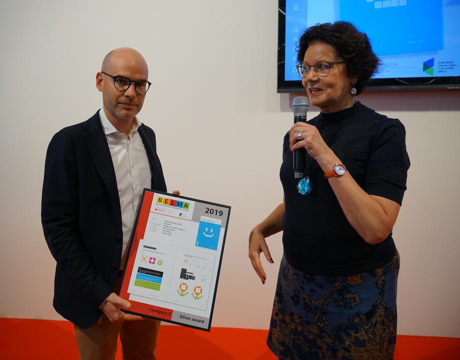 Helga Holtkamp (r) überreicht Verlagsleiter Manuel Schär die Auszeichnung. Quelle: BELMA